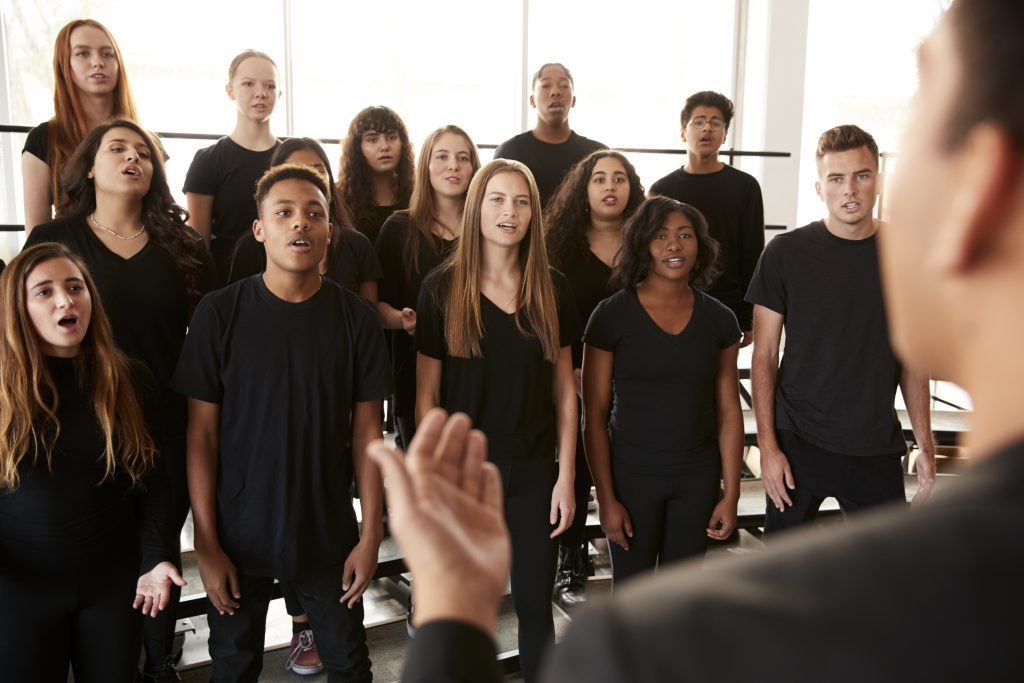 male and female students singing in a choir